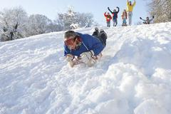 man sledging down hill with family watching - stock photo