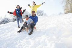family having fun sledging down snowy hill - stock photo
