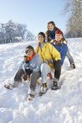 Stock Photo of family enjoying sledging down snowy hill