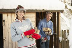 young couple collecting logs from wooden store in snow - stock photo