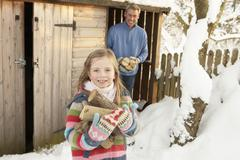 father and daughter collecting logs from wooden store in snow - stock photo
