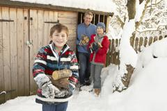 Stock Photo of family collecting logs from wooden store in snow