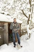 Middle aged man clearing snow from path to wooden store Stock Photos