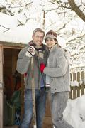 Young couple clearing snow from path to wooden store Stock Photos
