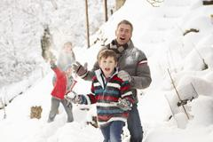 Family having snowball fight in snowy landscape Stock Photos