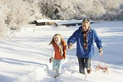 Father and daughter pulling sledge up snowy hill Stock Photos