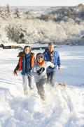 Father and children pulling sledge up snowy hill Stock Photos