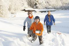 father and children pulling sledge up snowy hill - stock photo