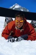 Stock Photo of Snowboarder lying on snowy hill wearing board and smiling (selective focus)