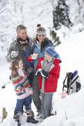 family stopping for hot drink and snack on walk through snowy landscape - stock photo
