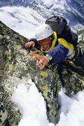 Stock Photo of Mountain climber coming up snowy mountain smiling (selective focus)
