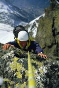 Mountain climber coming up snowy mountain smiling (selective focus) - stock photo