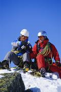 Two mountain climbers sitting on snowy mountain drinking from thermos and - stock photo
