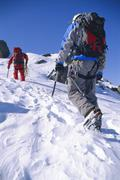 Two mountain climbers walking up snowy mountain (selective focus) - stock photo