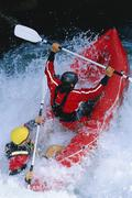Two kayakers rowing in rapids (selective focus) Stock Photos