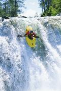 Kayaker in rapids coming over waterfall (selective focus) - stock photo