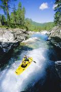 Kayaker rowing in rapids - stock photo