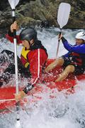 Two kayakers rowing in rapids and smiling (selective focus) Stock Photos