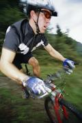 Man outdoors on trails riding bicycle (out of focus) - stock photo