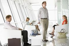 Male airline passenger waiting with other passengers in departure gate - stock photo