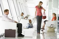 Female airline passenger waiting with other passengers in departure gate - stock photo