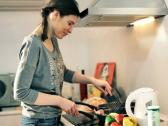 Young happy woman cooking in the kitchen NTSC Stock Footage