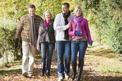 Two couples walking outdoors in park smiling - stock photo