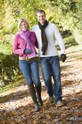 Couple outdoors walking on path in park smiling (selective focus) - stock photo