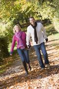 Couple outdoors running on path in park holding hands smiling (selective focus) Stock Photos