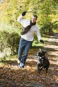 Man outdoors with dog on path in park holding branch smiling (selective focus) Stock Photos