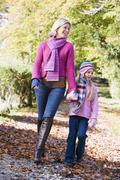 Woman and young girl walking outdoors in park and smiling Stock Photos