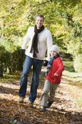 Man and young boy walking outdoors in park and smiling Stock Photos