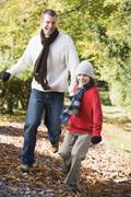 Man and young boy running outdoors in park and smiling - stock photo