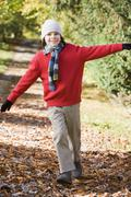Young boy outdoors at park running on path and smiling (selective focus) Stock Photos