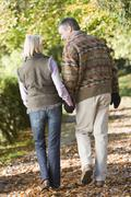 Couple outdoors walking on path in park holding hands and smiling (selective - stock photo
