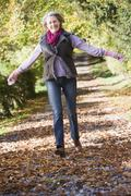 Woman outdoors at park running on path and smiling (selective focus) - stock photo