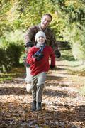 Grandfather and grandson running outdoors in park and smiling - stock photo