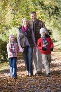 Grandparents walking with grandchildren outdoors in park and smiling - stock photo