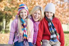 Mother and two young children outdoors in park smiling - stock photo