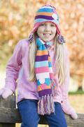 Young girl outdoors at park sitting on fence smiling (selective focus) - stock photo