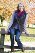 Woman outdoors at park sitting on fence smiling (selective focus) - stock photo