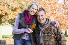 Couple outdoors in park by fence smiling (selective focus) - stock photo