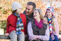 Grandparents with grandchildren outdoors in park smiling (selective focus) - stock photo