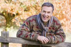 Mies ulkona puistossa nojaten aitaa hymyillen (valikoiva tarkennus) Kuvituskuvat