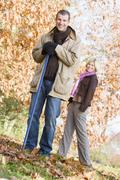 Man outdoors raking leaves and woman in background smiling (selective focus) - stock photo