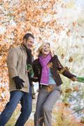 Couple outdoors playing in leaves and smiling (selective focus) Stock Photos