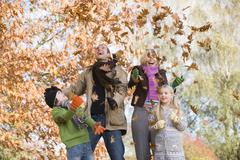 Stock Photo of Family outdoors in park playing in leaves and smiling (selective focus)