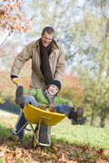 Man and young boy outdoors playing with wheelbarrow and smiling (selective Stock Photos