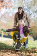 Man outdoors pushing woman in wheelbarrow and smiling (selective focus) - stock photo
