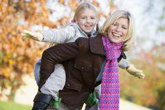 Mother outdoors piggybacking daughter and smiling (selective focus) Stock Photos